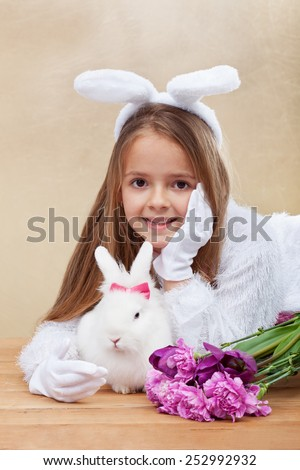 Cute bunnies with spring flowers - little girl with bunny ears and white rabbit- shallow depth of field - stock photo