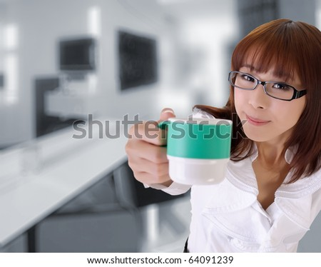 Cute business woman give you a cup of coffee in office. - stock photo
