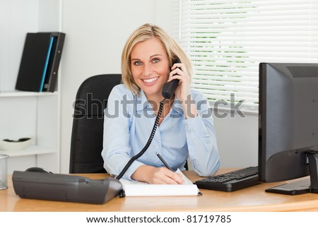 Cute businesswoman on phone writing something down looks into camera in her office - stock photo