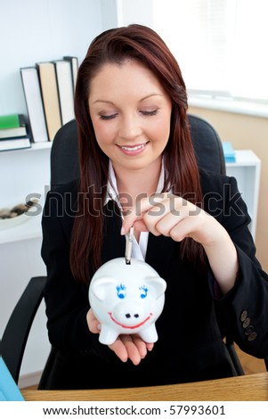 Cute businesswoman putting money in a  piggybank in her office - stock photo
