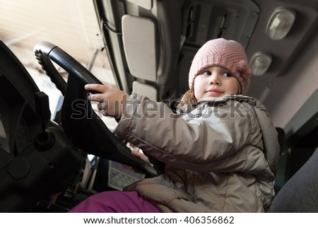 Cute Caucasian baby girl driving big cargo truck, close-up photo - stock photo