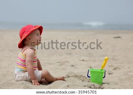Cute Caucasian baby girl playing with the sand on the beach.
