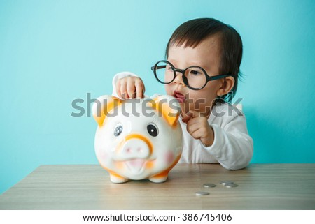 Cute caucasian baby playing with piggy bank
