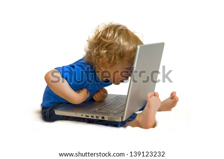 Cute caucasian boy child full lenght with laptop computer on his lap dressed in blue shirt and jeans, sitting on the floor and pointing interested isolated on white background - stock photo
