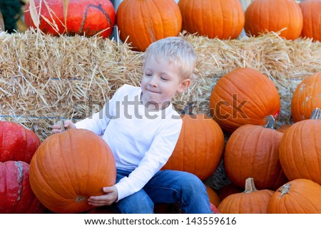 cute caucasian boy holding a big pumpkin at pumpkin patch