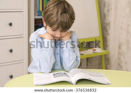 Cute caucasian boy reading a book at the green table. Horizontal color image - stock photo