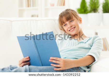 Cute Caucasian girl sitting on a sofa and reading a book. - stock photo
