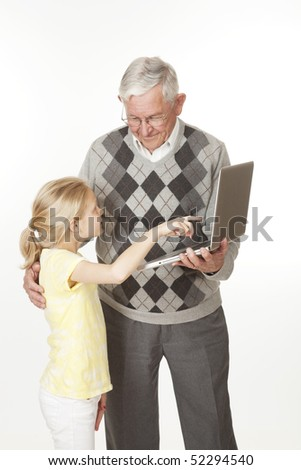 Cute Caucasian granddaughter showing her grandfather something on the computer - stock photo