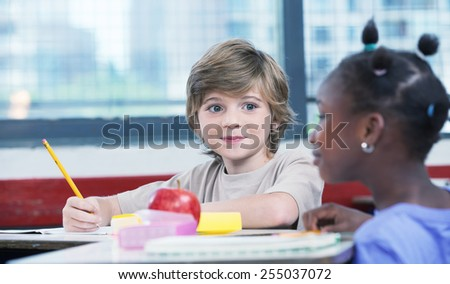Cute caucasian kid at classroom desk drawing and smiling to his afro american female friend. - stock photo