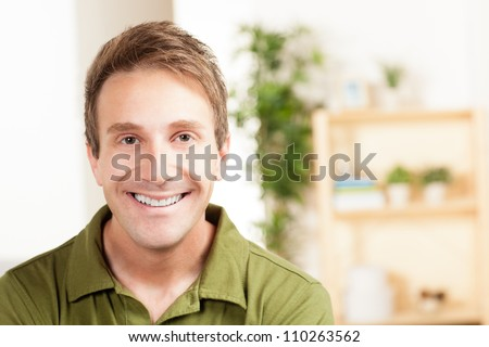 Cute Caucasian man relaxing at home in the living room with light hair wearing a green shirt and jeans.