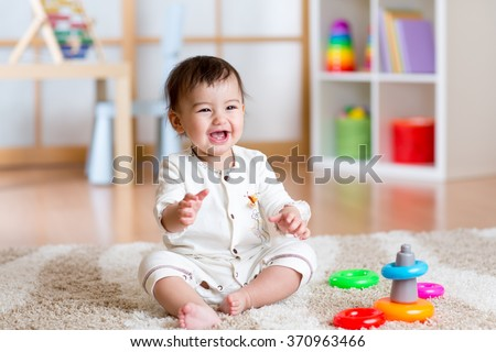 cute cheerful baby playing with colorful toy at home - stock photo
