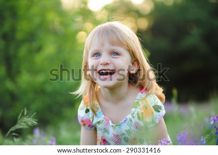 Cute cheerful blond girl playing in the park - stock photo