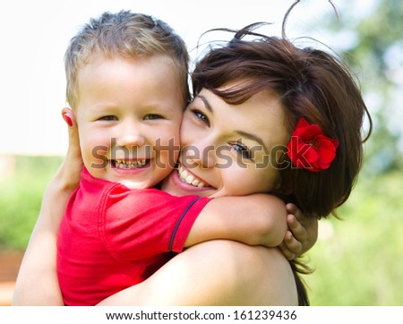 Cute cheerful boy is playing with his mother outdoors - stock photo