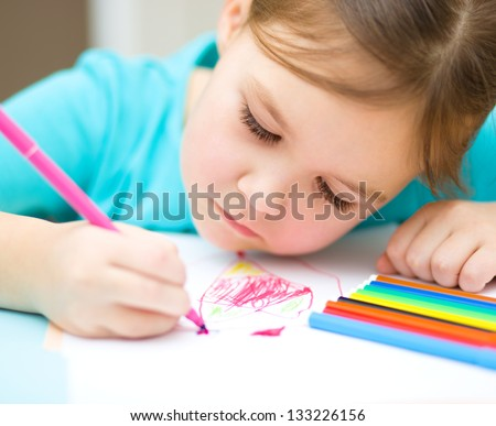 Cute cheerful child drawing using felt-tip pen while sitting at table - stock photo