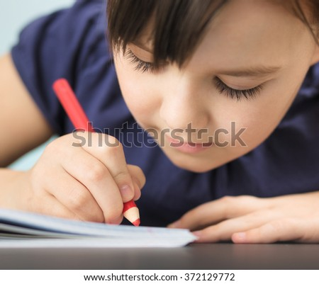 Cute cheerful child drawing using pencil while sitting at table, extreme closeup - stock photo