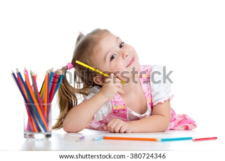Cute cheerful child drawing using pencils while lying on floor