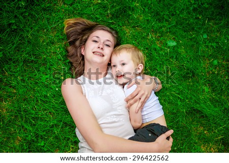 Cute cheerful child with mother play outdoors in park - stock photo