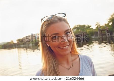 Cute Cheerful Female Enjoying Sunny Day Near River - stock photo