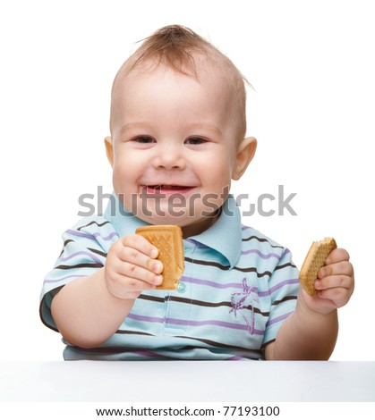 Cute cheerful little boy is holding cookies and smile, isolated over white - stock photo