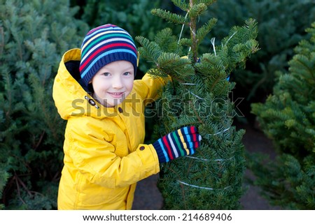 cute cheerful little boy shopping for christmas tree at winter - stock photo