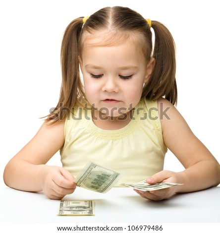 Cute cheerful little girl is counting dollars, isolated over white - stock photo