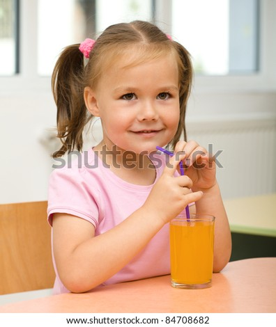 Cute cheerful little girl is drinking orange juice using straw