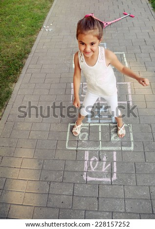 cute cheerful little girl playing hopscotch on playground outside  - stock photo