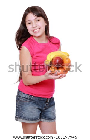 Cute cheerful little girl smiles while holding fruits