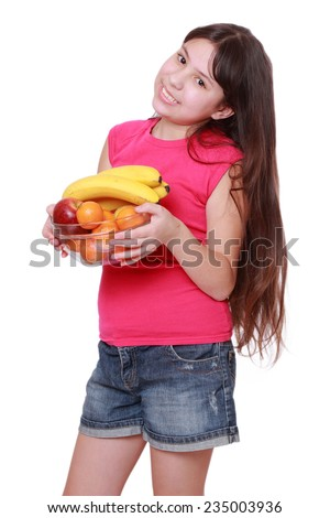 Cute cheerful little girl smiles while holding fruits isolated over white - stock photo