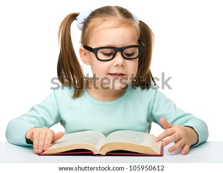 Cute cheerful little girl with books wearing glasses, isolated over white