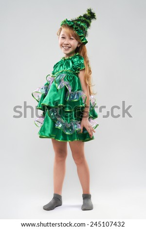 Cute cheerful red-haired girl in costume Christmas trees - stock photo