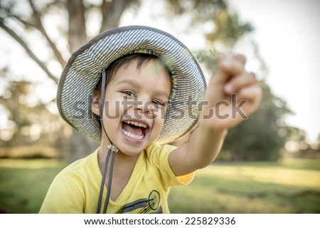 Cute cheerful 4 year old mixed race Asian Caucasian boy wearing a hat and playing outside in the summer sun - stock photo
