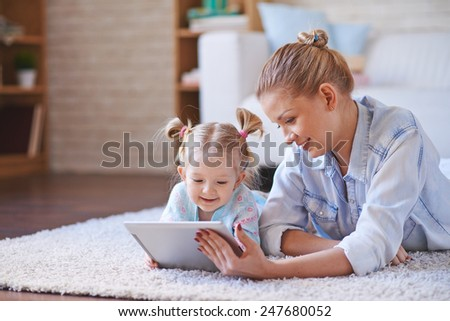 Cute child and her mother with digital tablet relaxing at home - stock photo