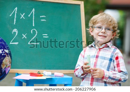 cute child at blackboard practicing mathematics, outdoor school or nursery. Back to school concept - stock photo