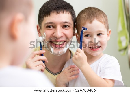 cute child boy and his daddy shave looking at mirror in bathroom - stock photo