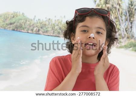 Cute Child boy  apply sunblock cream on his face on beach background - stock photo