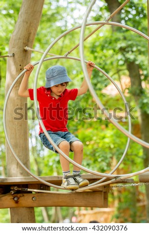 Cute child, boy, climbing in a rope playground structure, springtime