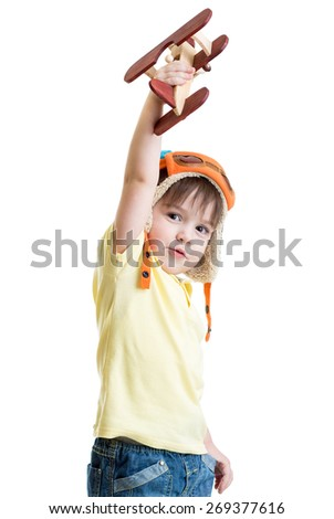 cute child boy dressed pilot and playing with wooden airplane toy - stock photo