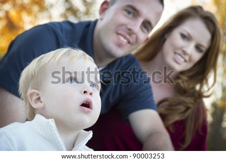 Cute Child Boy Looks Up to the Sky as Young Parents Smile.