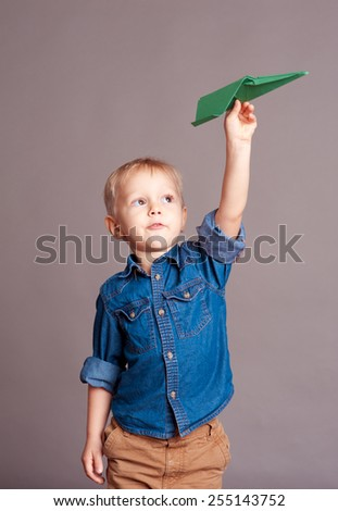 Cute child boy 3-4 year old playing with paper plane over gray. Playful baby. Wearing stylish clothes. Childhood.  - stock photo