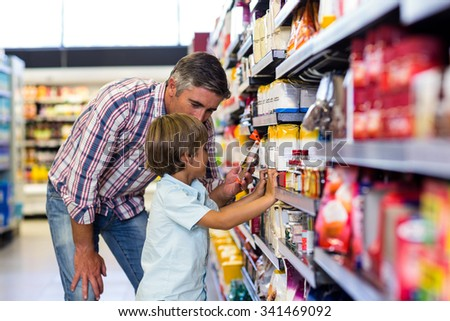 Cute child choosing food from shelf on supermarket - stock photo