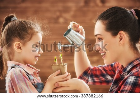 Cute child girl helps her mother to care for plants. Happy family engaged in gardening in the backyard. Mother and her daughter watering a growing sprout. Spring concept, nature and care. - stock photo