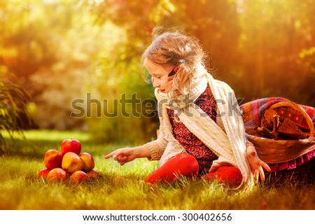 cute child girl in white knitted scarf with apples in sunny autumn garden - stock photo
