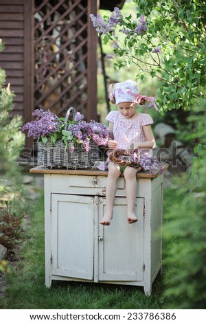 Cute child girl making lilac wreath in spring garden