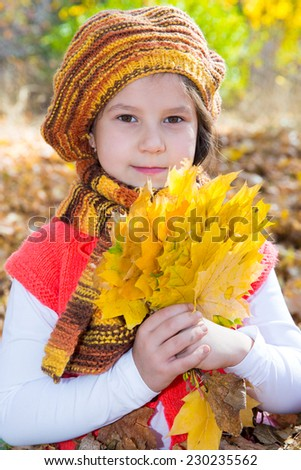 Cute child girl playing with fallen leaves in autumn park - stock photo