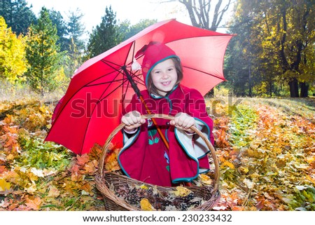 Cute child girl playing with umbrella in leaves in autumn park - stock photo