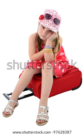 Cute child girl sitting on the luggage - stock photo