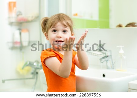 Cute child girl washing hands in bathroom - stock photo