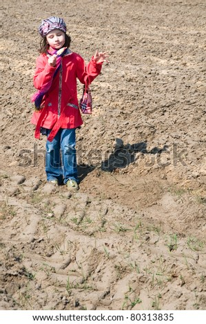 Cute child girl with ice cream playing in the field - stock photo