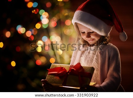 Cute child in Santa cap opening box with Christmas gift - stock photo